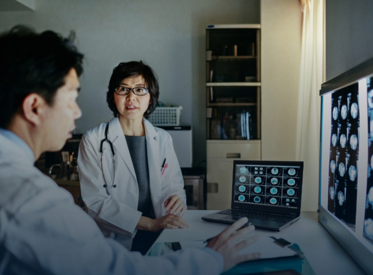 two doctors looking over mri images on a lenovo laptop
